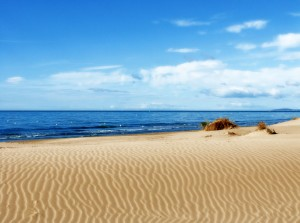 a mediterranean beach with blue skies and golden sand